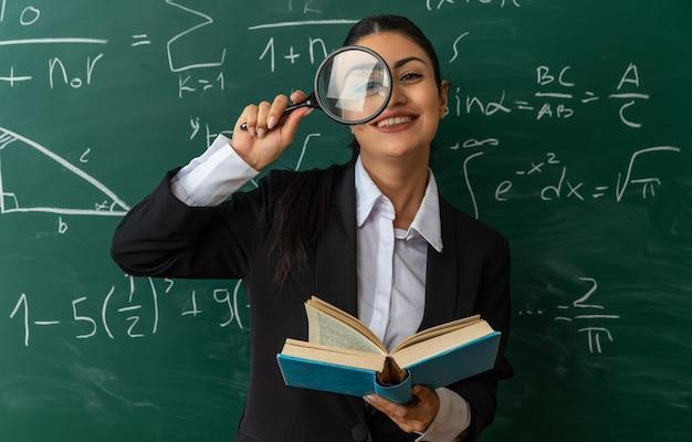 Jovem professora sorridente em pé na frente do quadro-negro, olhando para a câmera com lupa segurando o livro na sala de aula
