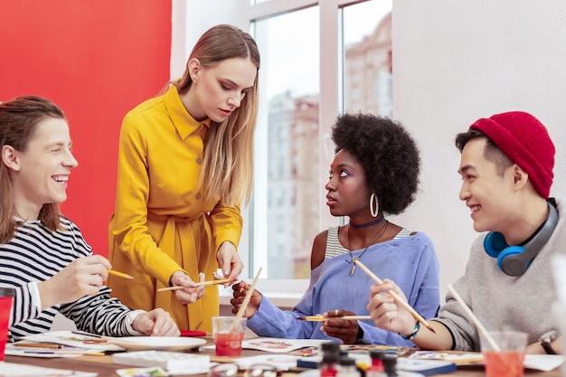 Jovem professora. três estudantes elegantes e bonitos olhando e ouvindo seu jovem professor