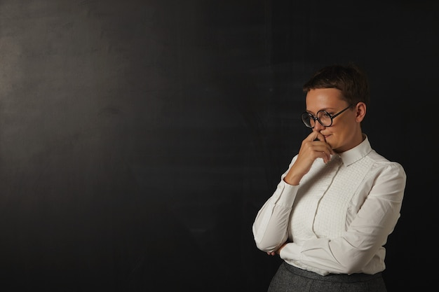 Jovem professora triste com uma blusa branca e saia cinza perdida em pensamentos ao lado de um quadro negro em branco