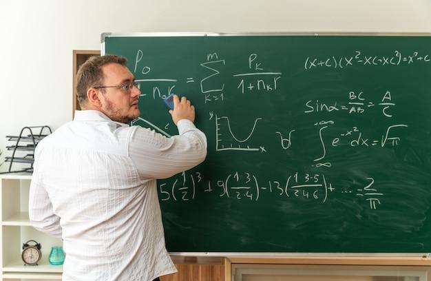 Jovem professora usando óculos atrás de vista na frente do quadro-negro na sala de aula, olhando para o lado, limpando o quadro-negro com borracha de giz