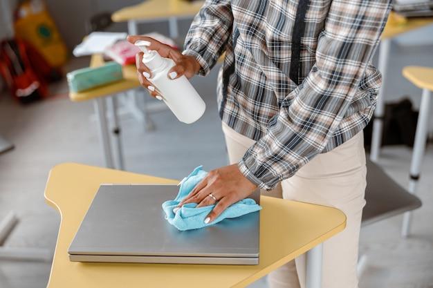 Jovem professora usando spray para desinfetar mesas na sala de aula