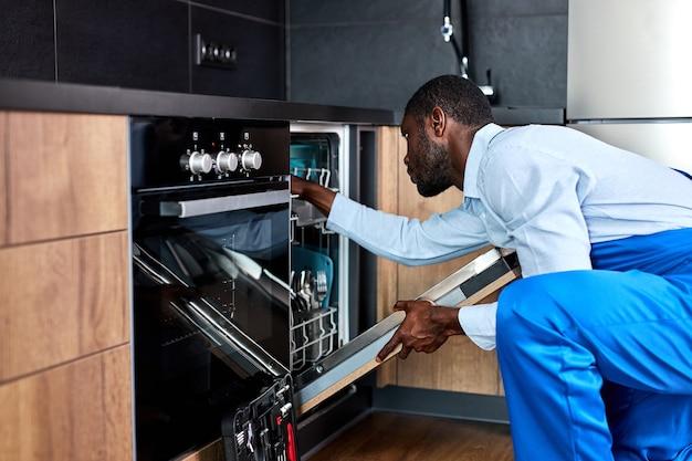 Jovem profissional afro-americano trabalhador manual com uniforme de macacão azul vai consertar a máquina de lavar louça, empreiteiro confiante examinando-a antes do conserto, parecendo sério, retrato de vista lateral.
