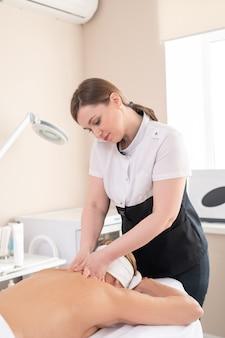 Jovem profissional de massagem em pé à mesa e relaxando os músculos do pescoço da mulher no procedimento de spa