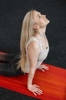 Jovem profissional fazendo exercícios para as costas na sala de fitness no tapete. a menina pratica ioga, alongamento ou pilates. estilo de vida esportivo.