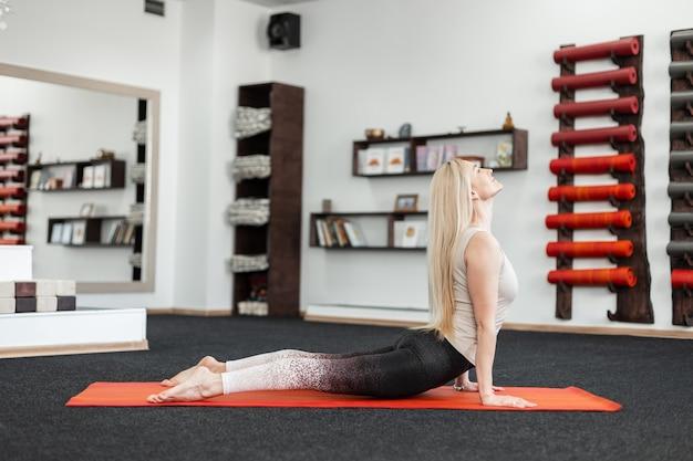Jovem profissional fazendo exercícios para as costas na sala de fitness no tapete. a menina pratica ioga, alongamento ou pilates.