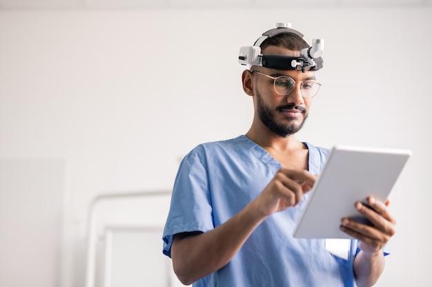 Jovem profissional médico com touchpad rolando por dados online enquanto trabalhava no hospital