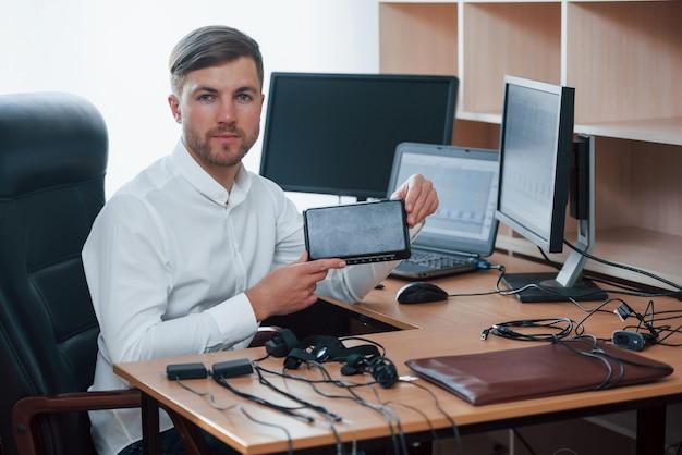 Jovem profissional. o examinador de polígrafo trabalha no escritório com seu equipamento detector de mentiras