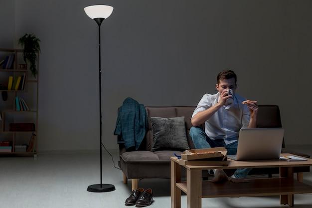 Jovem profissional tendo um lanche enquanto trabalhava em casa