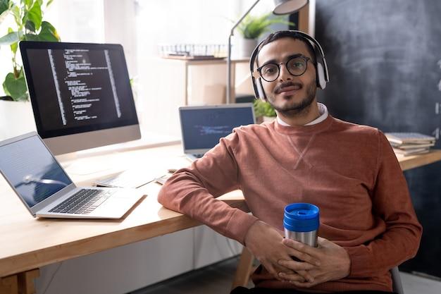 Jovem programador bonito em fones de ouvido, ouvindo música e bebendo enquanto está sentado na cadeira perto da mesa no intervalo