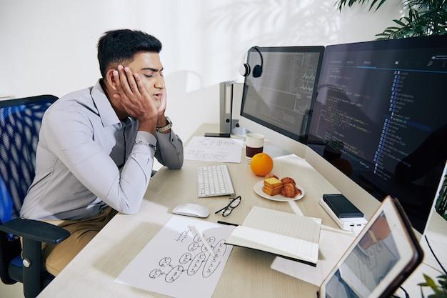 Jovem programador indiano cansado, quase dormindo em sua mesa depois de trabalhar em um projeto difícil o dia todo