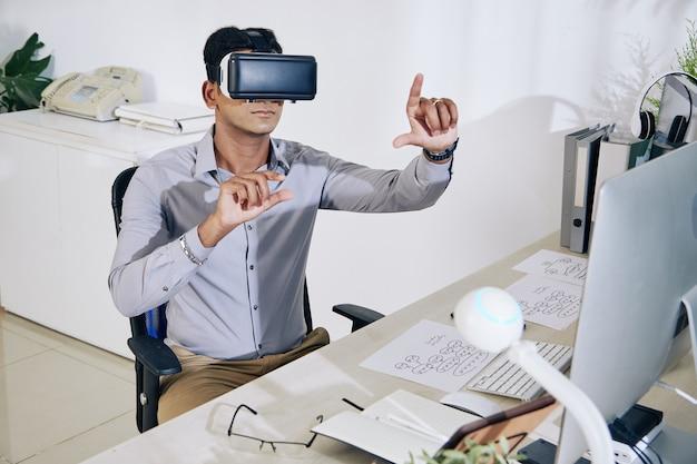 Jovem programador indiano sério em interface de teste de fone de ouvido para novo aplicativo de realidade virtual