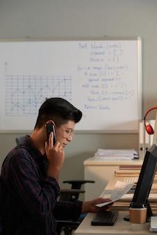 Jovem programador olhando documento com fluxograma de projeto e falando ao telefone com colegas de ...
