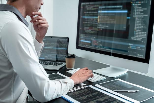 Jovem programador trabalhando em software javascript para computador em escritório de ti, escrevendo códigos e códigos de dados para sites e codificando tecnologias de banco de dados para encontrar solução para o problema. Foto Premium