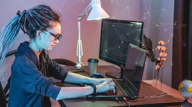 Jovem programadora moderna está escrevendo o código do programa em um laptop em casa