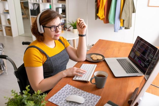 Jovem programadora sentada à mesa em casa, comendo biscoitos com chá e trabalhando com dados na frente da tela do computador e laptop