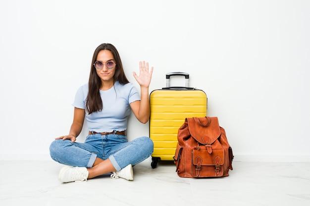Jovem pronta para ir viajar sorrindo alegre mostrando o número cinco com os dedos