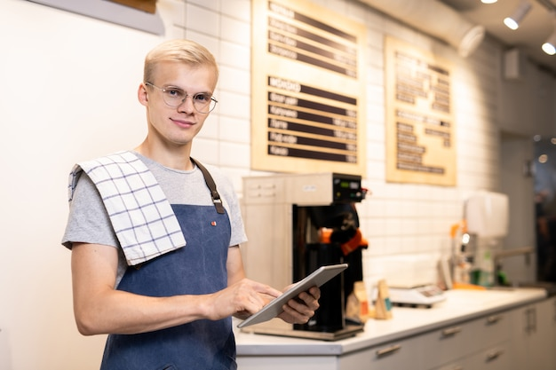 Jovem proprietária de lanchonete bem-sucedida com touchpad olhando para você enquanto recebe pedidos de bebidas de clientes online