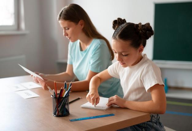 Jovem psicóloga ajudando uma garota na terapia da fala