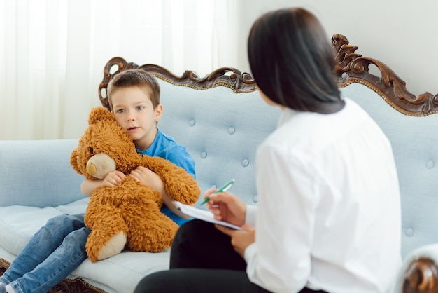 Jovem psicóloga trabalhando com garotinho no escritório