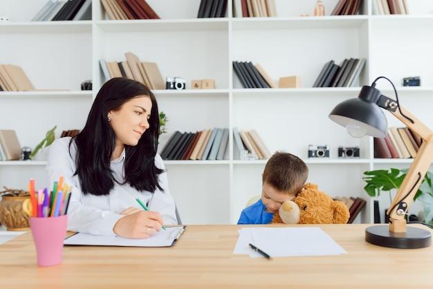 Jovem psicóloga trabalhando com uma criança pequena no escritório