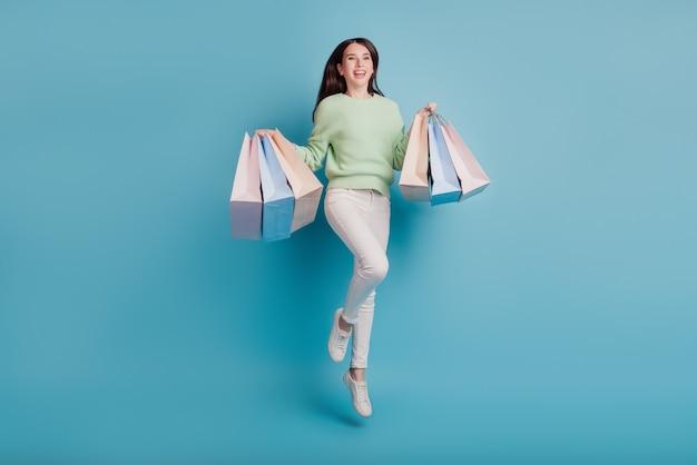 Jovem pula carregando sacolas de compras isoladas em fundo azul