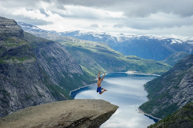 Jovem pula na borda trolltunga. noruega.