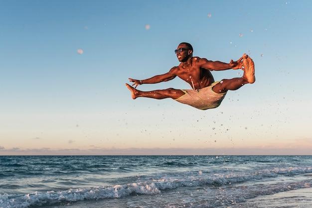Jovem pulando na praia. atitude feliz.