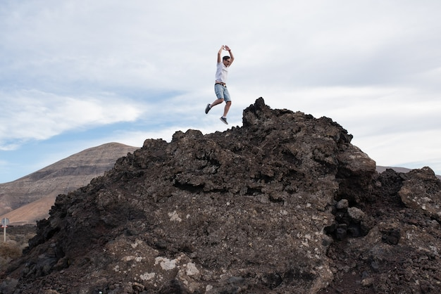 Jovem pulando no topo de uma montanha.
