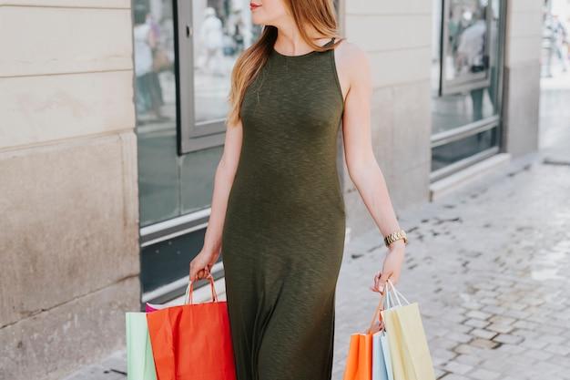 Jovem que anda na cidade com sacolas de compras