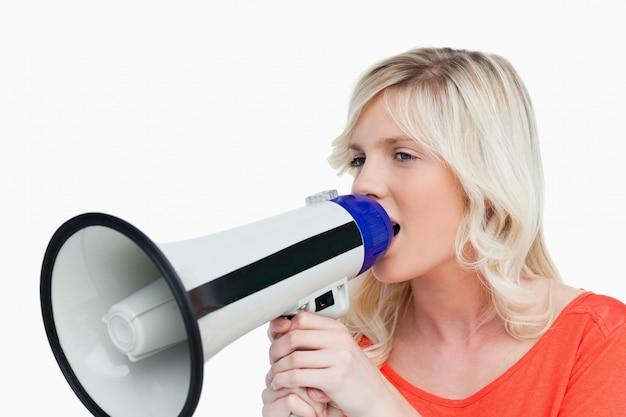 Jovem que olha para o lado enquanto fala em um megafone