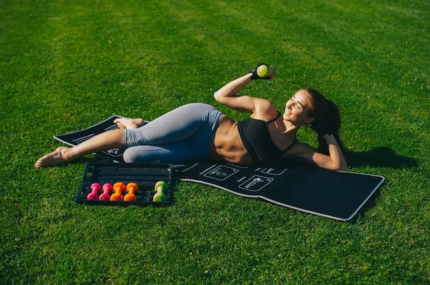 Jovem que se exercita. ajude a morena desportiva a fazer uma prancha na esteira de ioga. conceito de estilo de vida e esportes saudáveis.