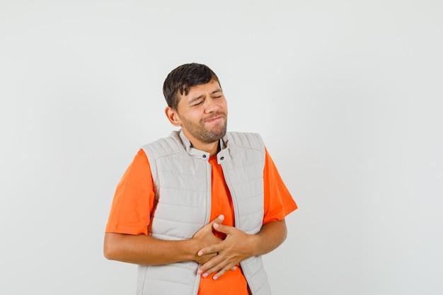 Jovem que sofre de dor de estômago em uma camiseta, jaqueta e parece desconfortável.