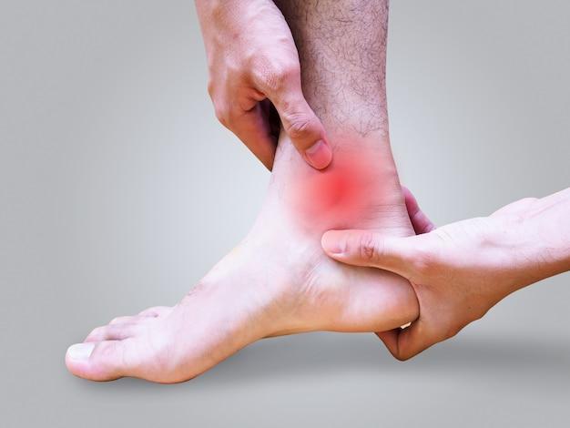 Jovem que sofre de dor no pé e tornozelo ou torção no tornozelo.