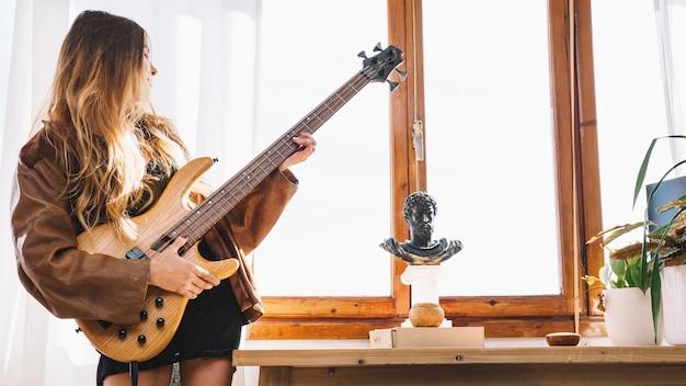 Jovem que toca violão em casa Foto gratuita