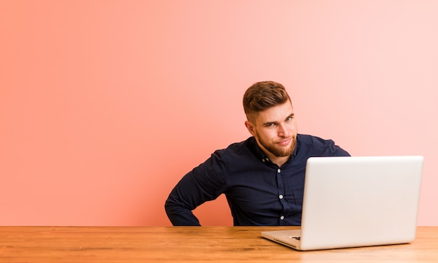 Jovem que trabalha com seu laptop, repreendendo alguém muito zangado.