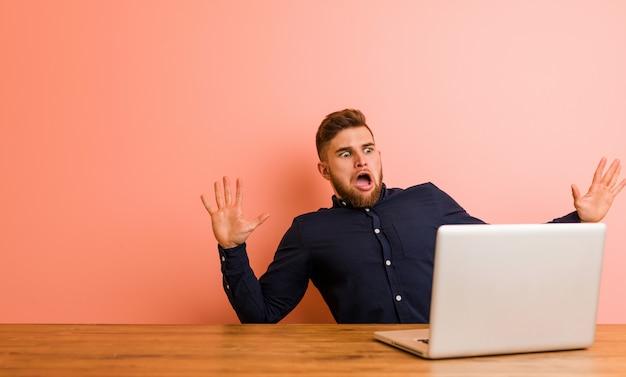 Jovem que trabalha com seu laptop sendo chocado devido a um perigo iminente
