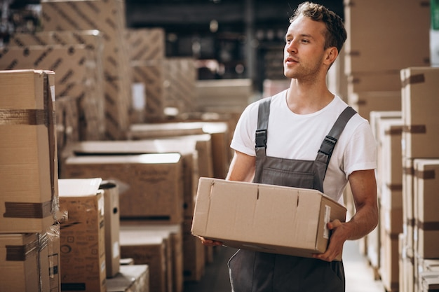 Jovem que trabalha em um armazém com caixas