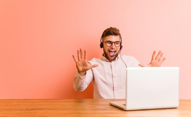 Jovem que trabalha em um call center, mostrando o número dez com as mãos.