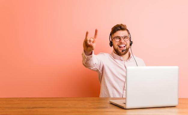 Jovem que trabalha em um call center, mostrando um gesto de chifres como um conceito de revolução.