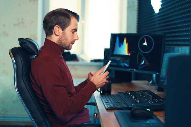 Jovem que trabalha no estúdio usando um smartphone e um computador. freelancer caucasiano, segurando o telefone móvel, trabalhando em filmagens, vídeo, design.