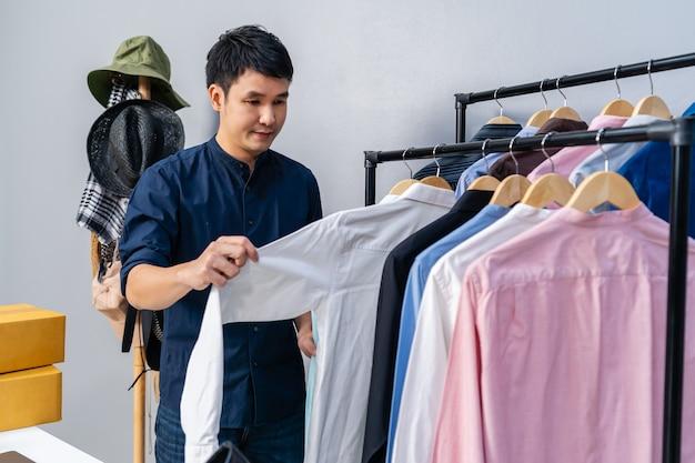 Jovem que vende roupas e acessórios online pela câmera de streaming ao vivo. comércio eletrônico on-line empresarial em casa