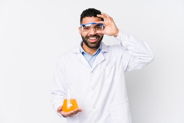 Jovem químico árabe isolado animado mantendo o gesto ok no olho.