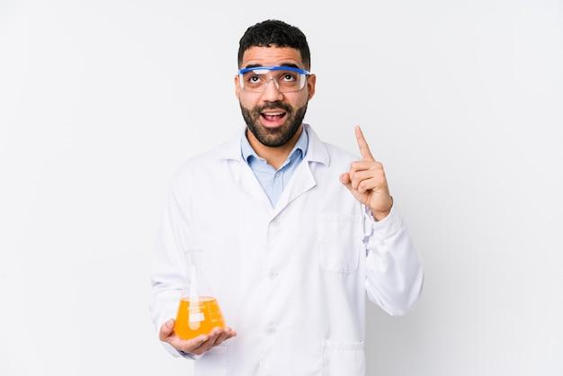 Jovem químico árabe isolado apontando para cima com a boca aberta.