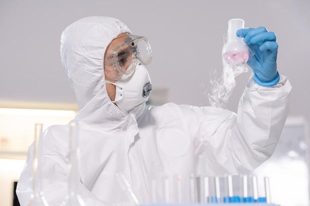 Jovem químico ou farmacêutico de macacão, máscara, óculos e luvas olhando para o bico com substância fumegante em laboratório