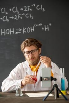 Jovem químico profissional vestindo jaleco branco, jogando fluido no bico com substância líquida rosa enquanto está sentado em frente à câmera do smartphone