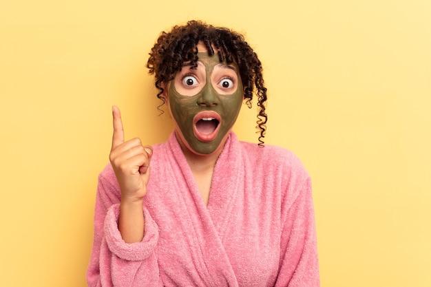 Jovem raça mista usando máscara facial isolada em fundo amarelo, tendo uma ideia, o conceito de inspiração.