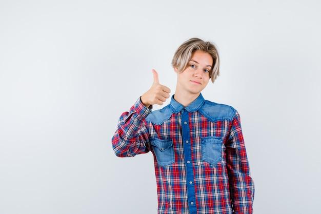 Jovem rapaz adolescente aparecendo o polegar em uma camisa e olhando alegre, vista frontal.