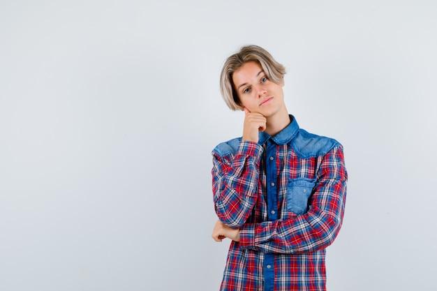 Jovem rapaz adolescente apoiando o queixo na mão em uma camisa e olhando pensativo, vista frontal.