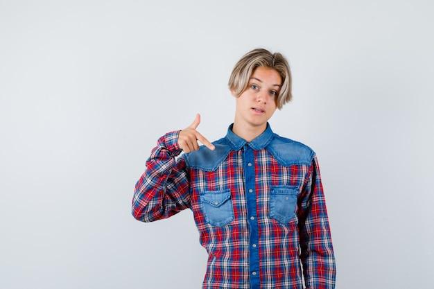 Jovem rapaz adolescente apontando para baixo em uma camisa xadrez e parecendo hesitante. vista frontal.