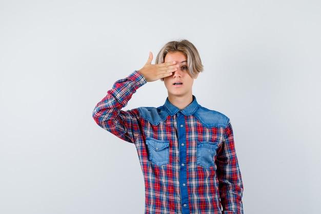 Jovem rapaz adolescente com a mão no olho em uma camisa e olhando maravilhado. vista frontal.